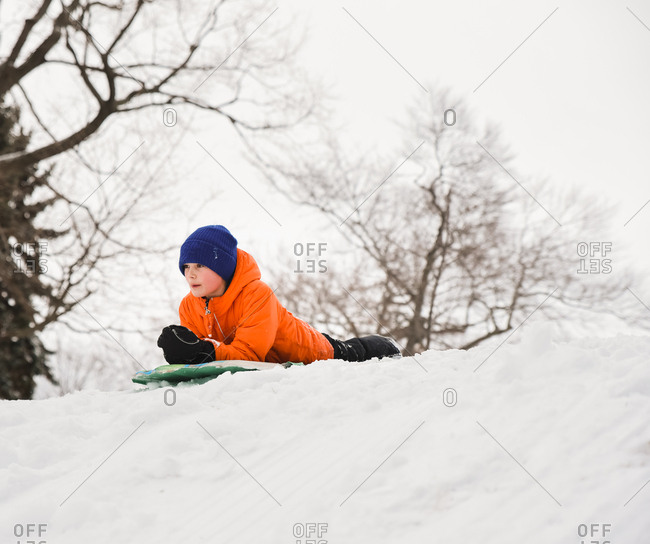 Boy laying on a sled on top of a snow covered hill on a winter day.