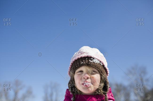Blonde Preschool Girl Eating Snow Stands Against Blue Sky
