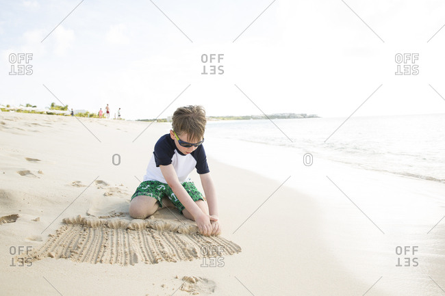 Young Boy Starts Sand Castle at Edge of Caribbean Sea
