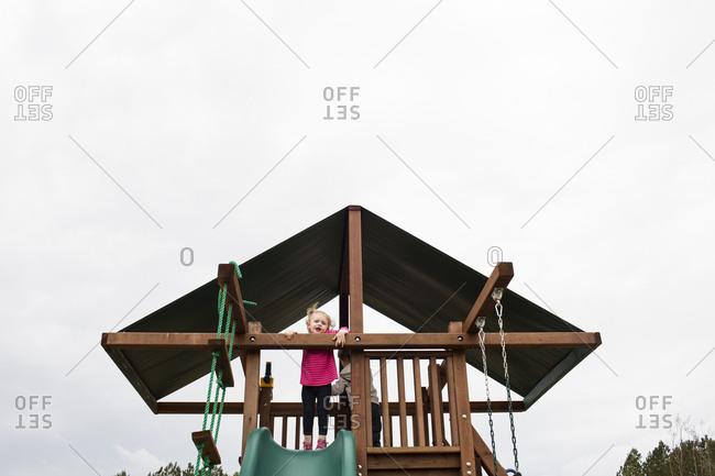 Cute Blonde Preschool Girl Plays on Top of Playground Set