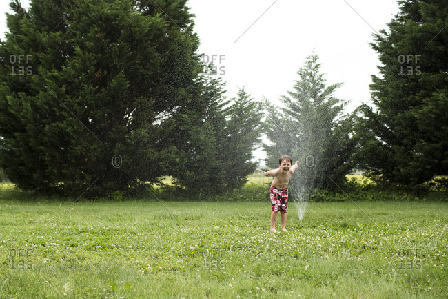 Kindergarten Boy Laughs in Delight While Running Through Sprinkler