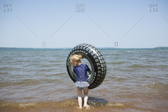 Blonde Toddler Girl Carries Large Tire Floatie into Lake Michigan
