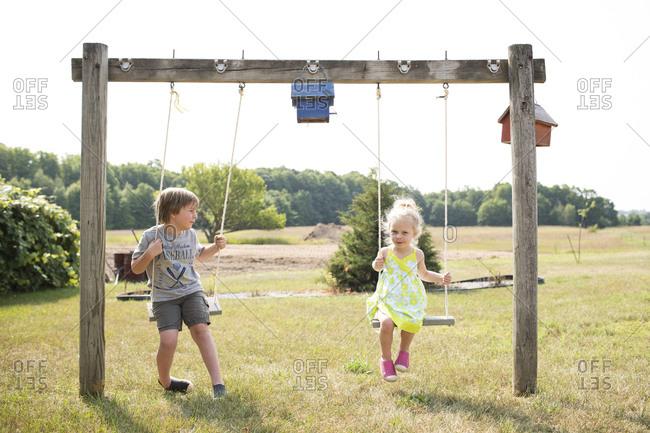 Blonde Siblings Play Together on Wooden Swings in Farm Field