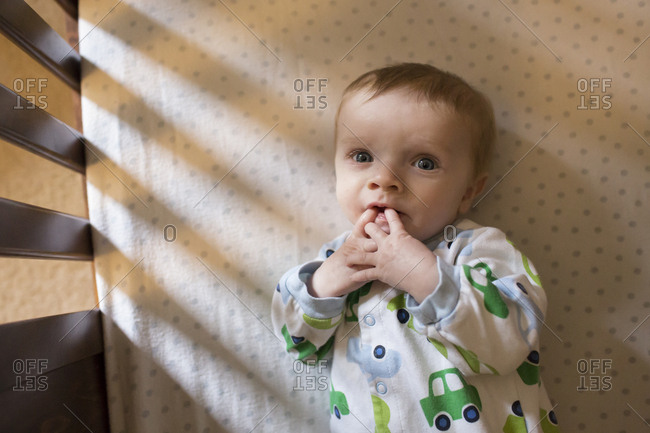 Blue Eyed Baby Boy Laying in Crib Looks Up, Makes Eye Contact