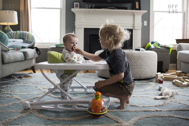 Baby Brother Standing in Walker Eats out of Big Brother's Hand