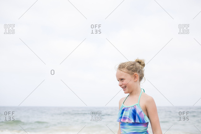 Smiling Young Blonde Curly Haired Girl in Bathing Suit, Ocean Behind