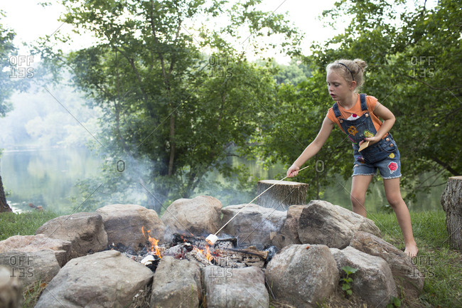 Blonde Girl in Overalls Roasts Marshmallow Over Campfire