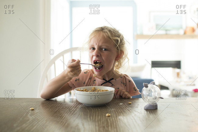 Blonde Girl Missing Front Tooth Eats Cereal at Bright Kitchen Table