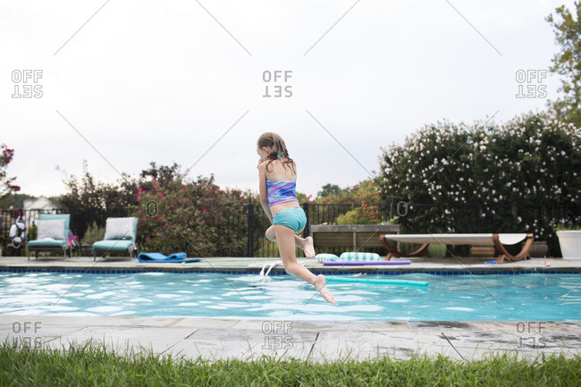 Rear View of Blonde Girl Jumping Into Backyard Swimming Pool
