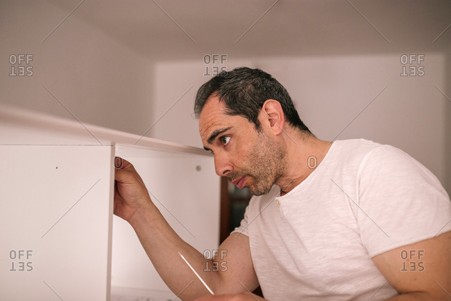 Man in his house assembling a table