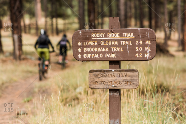 Trail sign with mountain bikers riding in the distance