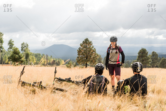 Mountain bike friends resting while on meadow trail
