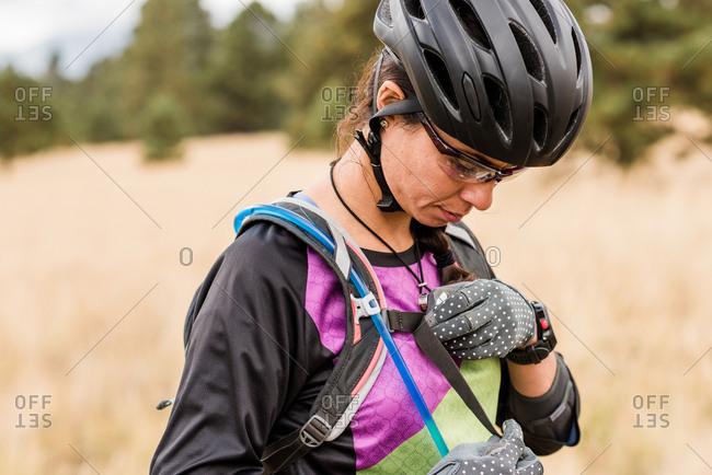 Female mountain biker adjusting backpack strap