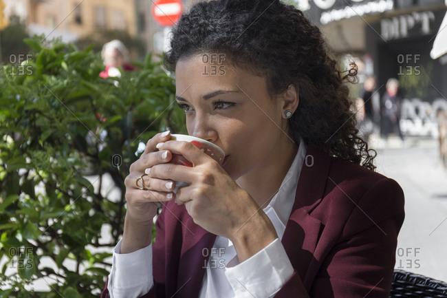 Portrait of stylish woman having coffee at coffee shop terrace