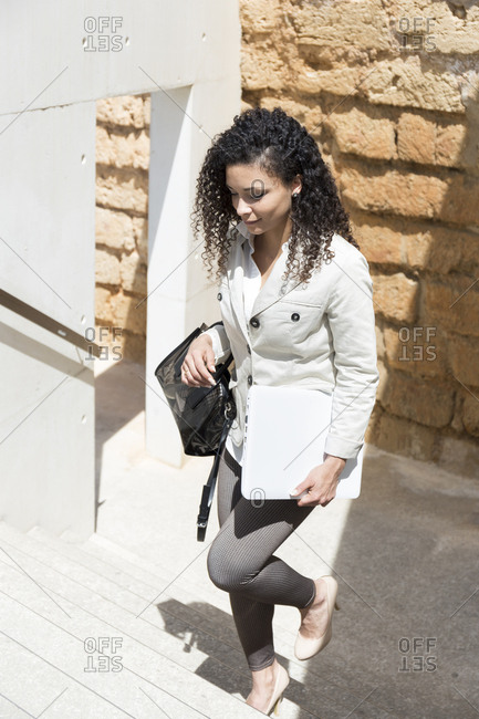 Business stylish woman with curly hair against a concrete wall