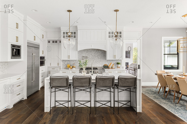 Beautiful white kitchen in new luxury home, with waterfall island