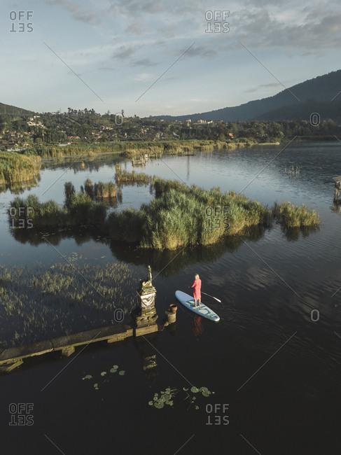 A female paddle boarding on a lake