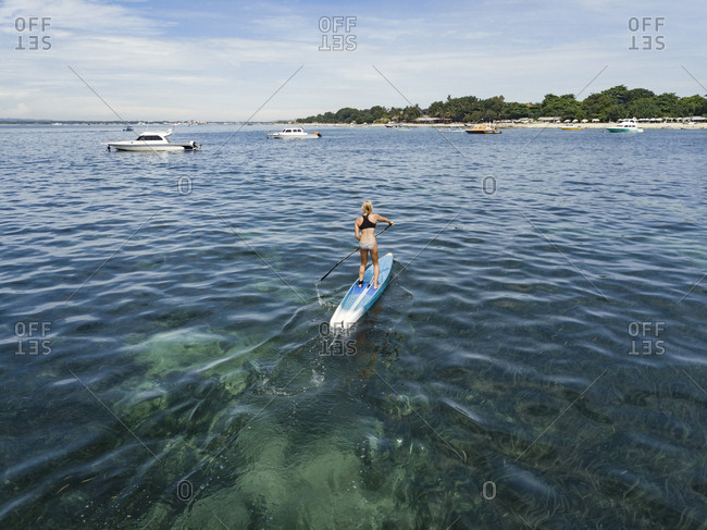 Young woman on stand up paddling board