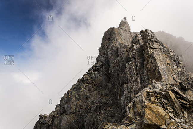 Figure rappelling from the top of a mountain buttress in New Zealand