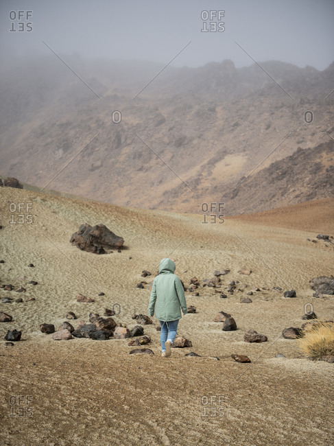 Rear view of woman walking through desert area against mountain in fog