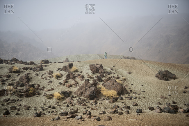 Woman standing on a hill in desert rocky area against mountains in fog