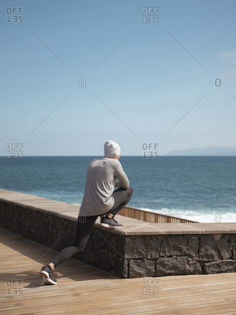 Young Athletic Man Doing Stretching Exercise For Legs On The Seaside