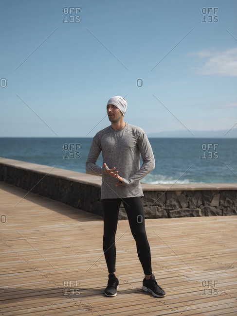 Young Man In Sportswear Standing On Seaside After Workout Against Sky