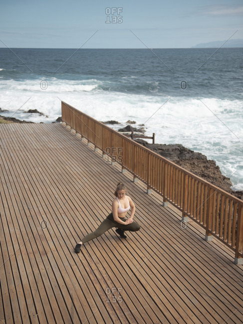 Young Adult Woman Doing Stretching Exercise For Legs At The Seaside