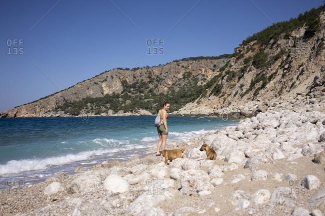 Woman walking with dogs by rocky coastline against Mediterranean sea