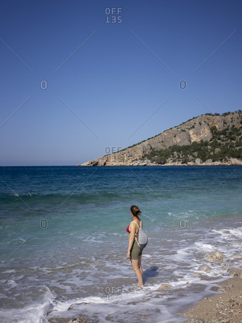 Rear view of woman enjoying the sun on the coast of Mediterranean sea