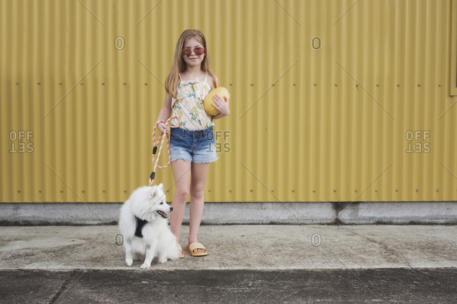 Young girl standing in front of a yellow wall holding a melon with dog