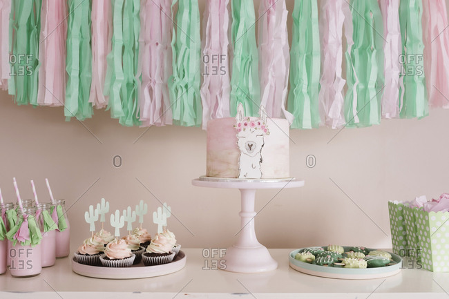 Llama birthday cake on a green and pink themed dessert table