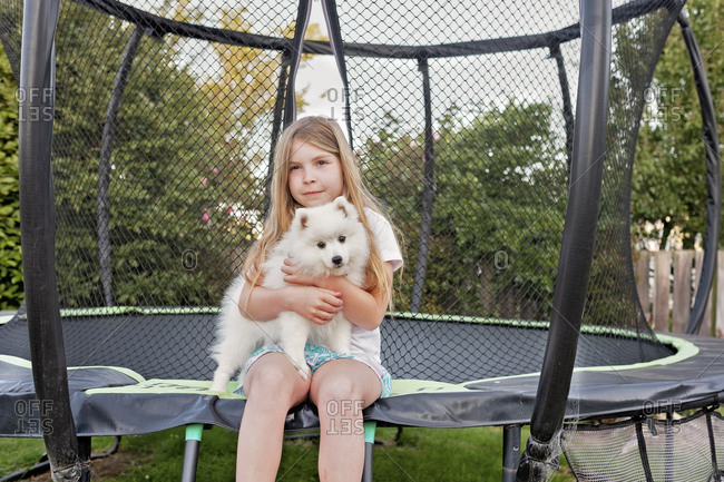 Young girl sitting on a trampoline holding a small fluffy white dog