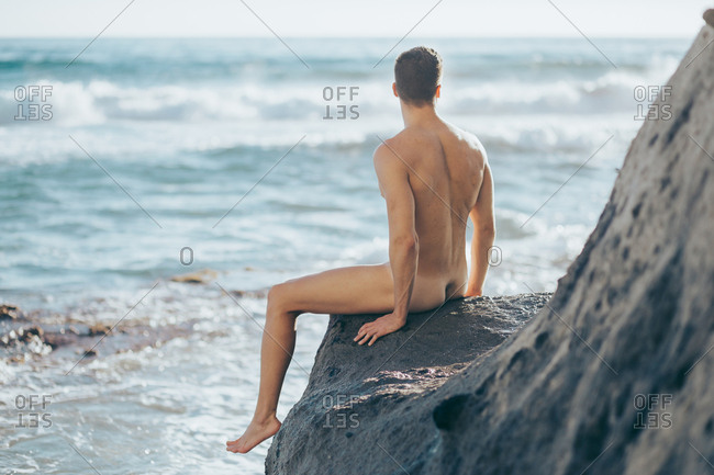 naked and strong man sitting on a rock on the sea