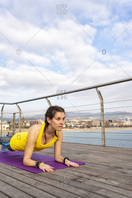 Side view of woman in sportswear sitting on mat, stretching on pier