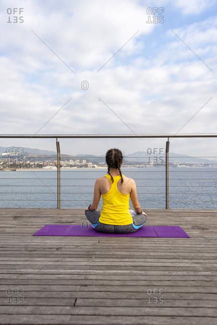 Rear view of woman in sportswear sitting on mat, stretching on pier
