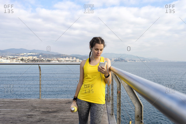 Woman athlete holding mobile phone and listening to music on earphones