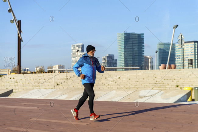 Full length of senior man jogging while exercising at park in winter