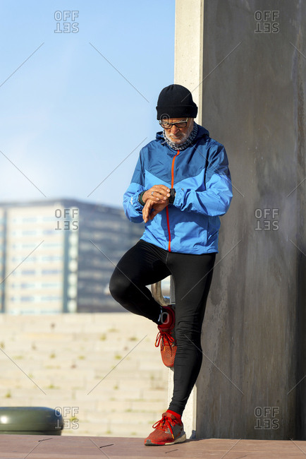 senior man with headphones looking at wristwatch while exercising