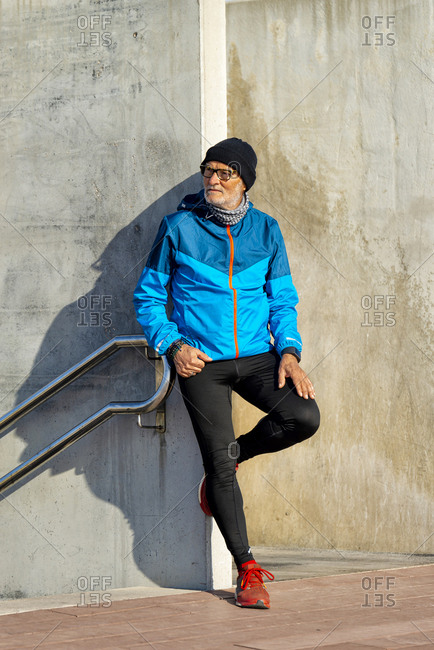 Senior man wearing sports clothes leaning on wall while looking away