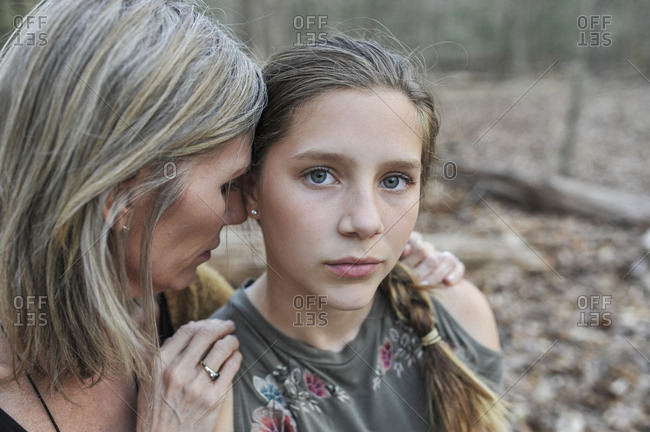 Mother hugging teenager daughter with blue eyes