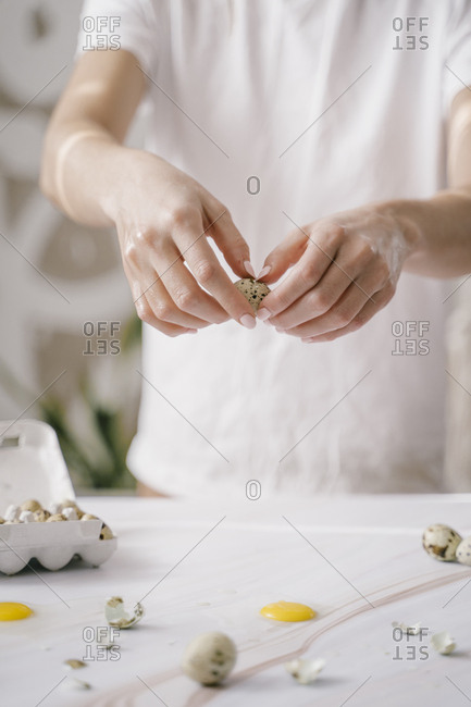 breaking egg yolk on marble. quail egg shell in hand. photo easter