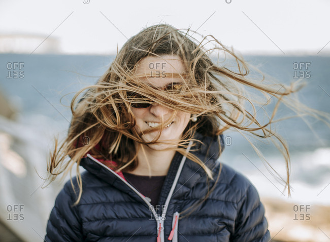 A young woman has her hair blown by the wind on the island of Malta.