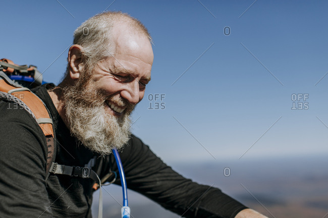 Retirement age hiker with a beard smiles at the top of Mount Katahdin