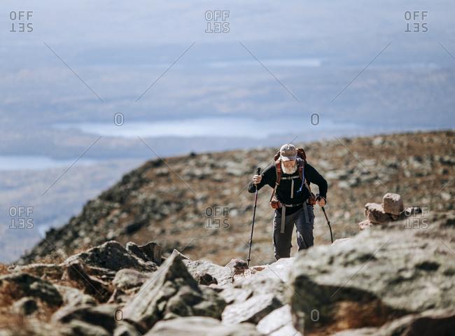 A retired male Appalachian Trail hiker walks along Mount Katahdin