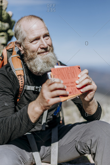 A male Appalachian Trail hiker holds congratulation cards.