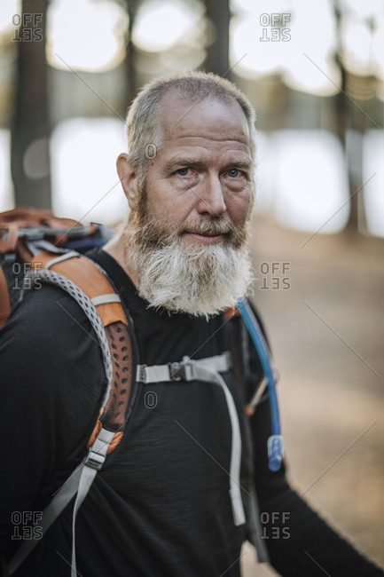 A portrait of a grey bearded retiree hiker with a backpack in Maine