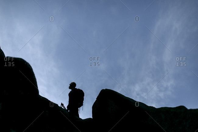 A silhouette of a hiker with a beard against the sky between boulders