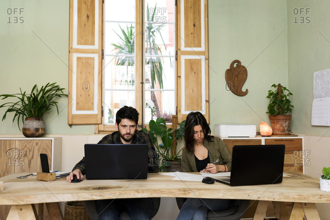 two designers working in his wooden table office in Barcelona