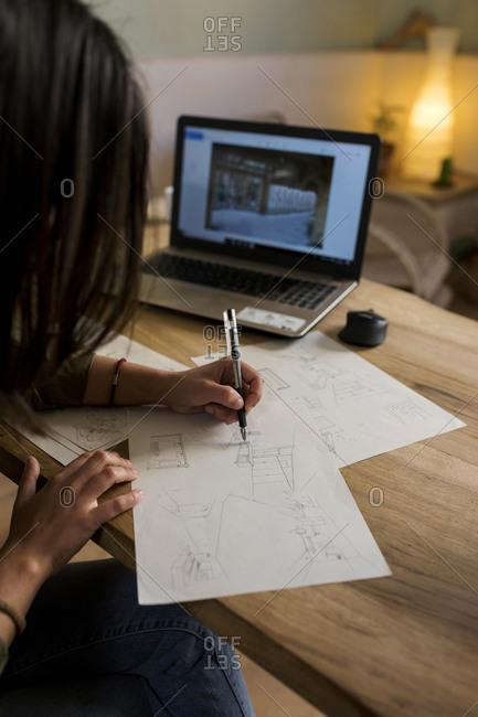 Young brunette interior designer making sketch at her atelier